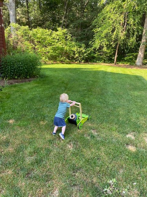 Picture of a toddler mowing the lawn with a toy lawn mower